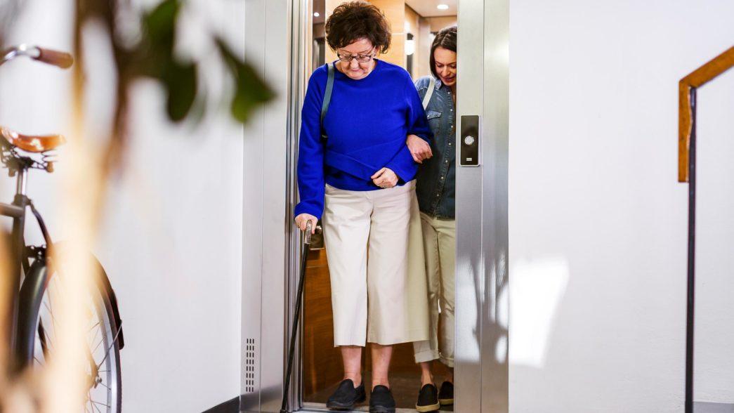 Persona con bastone che usa l'ascensore