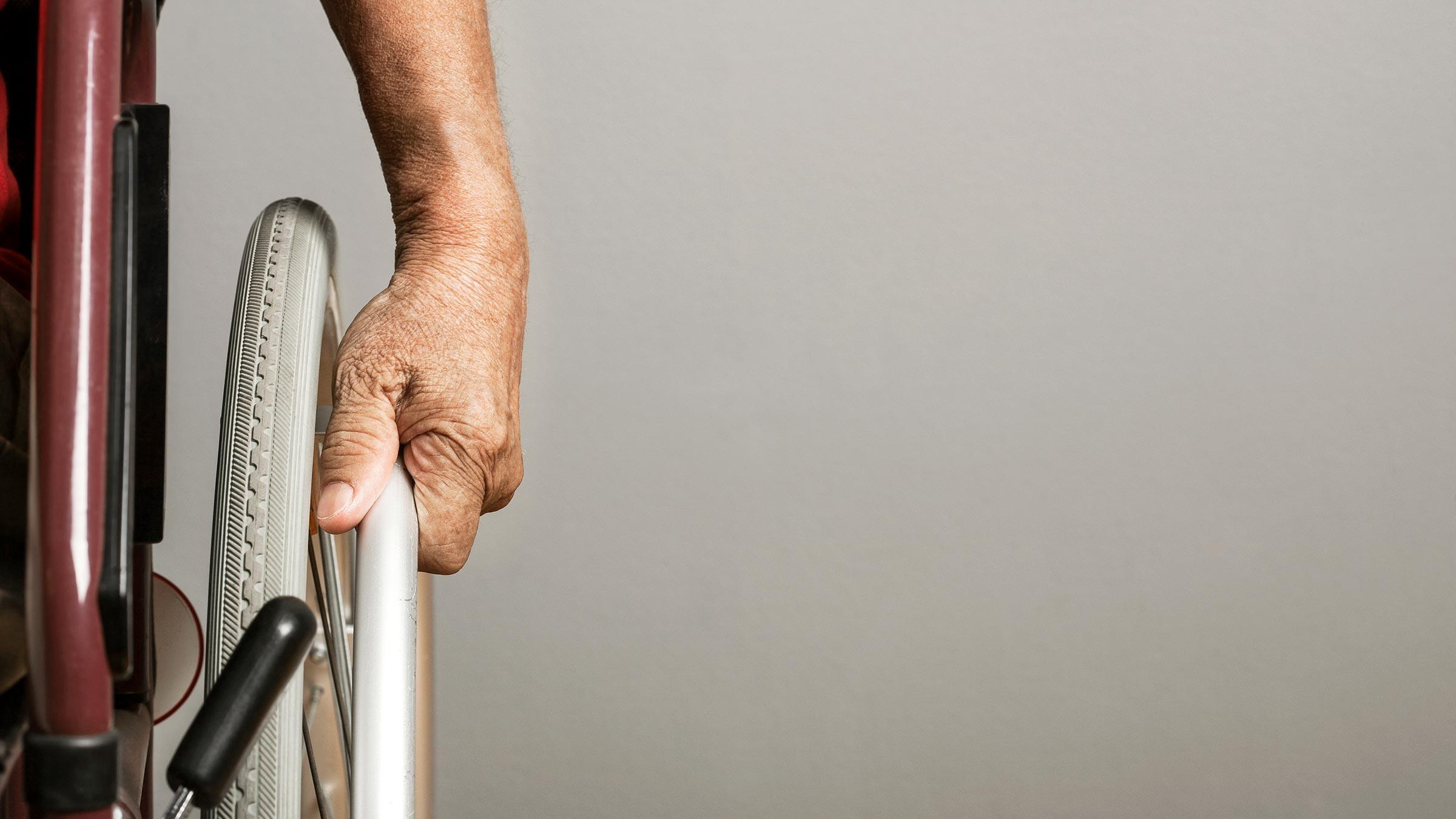 Closeup di una mano che manovra una sedia a rotelle
